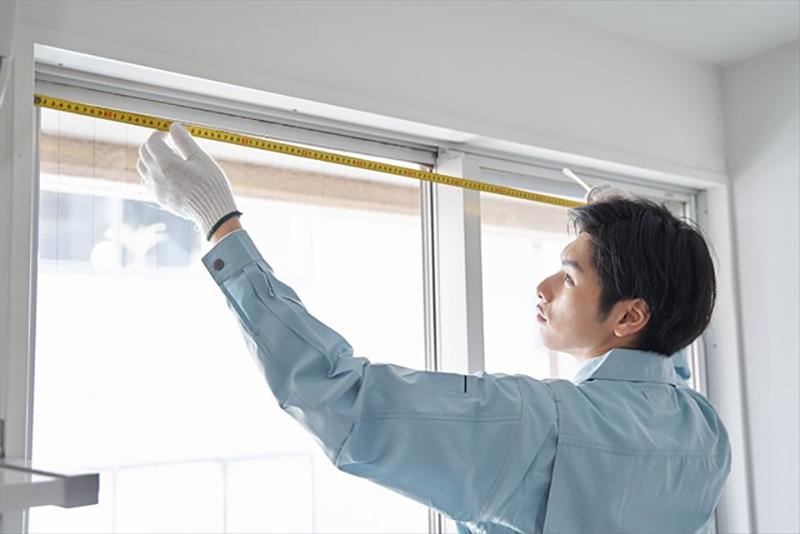 窓枠のサイズを測る日本人男性